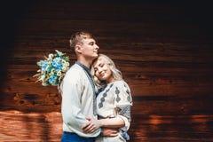 Zadziwiająca ślub para w embroidereds koszulowi z wiązką kwiaty na tle drewniany dom zdjęcia stock