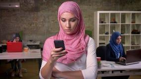 Zadziwiająca arabska kobieta w różowym hijab stoi oddzielał od innych dziewczyn w ceglanym biurze i scrolling jej telefon
