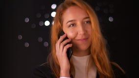 Zadziwiająca caucasian rudzielec kobieta jest stojąca i opowiadająca nad telefonem na czarnym tle, pozytywnie patrzeje na boku i