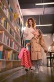 Zadziwiająca dziewczyna utrzymuje papierowe torby w prawej ręce obrazy stock