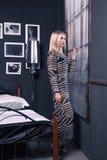 Zadziwiająca dziewczyna w przejrzystej sukni patrzeje out okno z zamyka fotografia stock