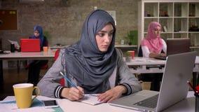 Zadziwiająca islamska dziewczyna robi notatkom i patrzeje spokojnie przy jej komputerem, podczas gdy siedzący przy desktop dalej,