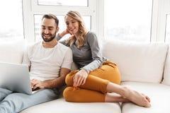Zadziwiająca kochająca para siedzi indoors w domu używać laptop obrazy royalty free