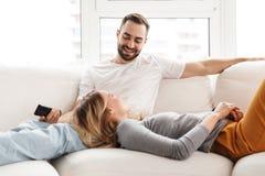 Zadziwiająca kochająca para siedzi indoors w domu zegarka TV mienia pilota do tv zdjęcia royalty free