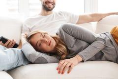 Zadziwiająca kochająca para siedzi indoors w domu zegarka TV mienia pilota do tv obrazy stock