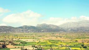 Zadziwiająca krajobrazowa dolina z polami na tło górach z niebieskim niebem Zdjęcia Stock