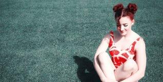 Zadziwiająca młoda rudzielec pozuje na trawie obraz royalty free