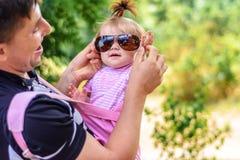 Zadziwiająca mała dziewczynka bawić się z okularami przeciwsłonecznymi z jej ojcem obrazy stock