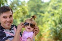 Zadziwiająca mała dziewczynka bawić się z okularami przeciwsłonecznymi z jej ojcem obraz stock