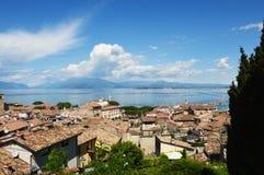 Zadziwiająca panorama od Desenzano kasztelu na Jeziornym Gardzie z starymi miasto dachami, górami, biel chmurami i żaglówkami na  Fotografia Stock