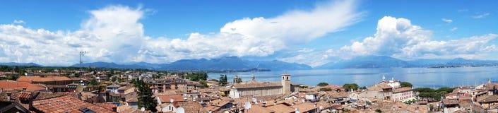 Zadziwiająca panorama od Desenzano kasztelu na Jeziornym Gardzie z starymi miasto dachami, górami, biel chmurami i żaglówkami na  Zdjęcia Royalty Free