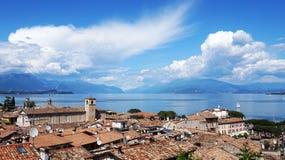 Zadziwiająca panorama od Desenzano kasztelu na Jeziornym Gardzie z starymi miasto dachami, górami, biel chmurami i żaglówkami na  Obrazy Royalty Free