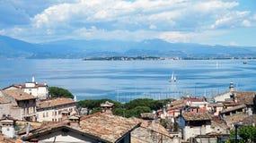 Zadziwiająca panorama od Desenzano kasztelu na Jeziornym Gardzie z starymi miasto dachami, górami, biel chmurami i żaglówkami na  Zdjęcie Royalty Free