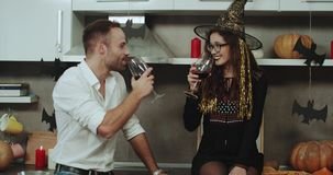 Zadziwiająca para przy Halloween przyjęciem romantycznego czas w kuchni z pięknymi Halloweenowymi dekoracjami, pije a zbiory wideo