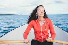 Zadziwiająca piękna z włosami dziewczyna pływa na drewnianym wioślarstwie z wiosłami w wspaniałym wiosny jeziorze i łodzi Styl ży zdjęcia royalty free