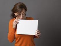 Zadziwiająca w średnim wieku kobieta patrzeje w dół przy strasznym białym panelem Obraz Stock