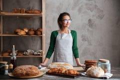 Zadziwiającej młodej damy piekarniana pozycja przy piekarnią blisko chleba Zdjęcia Stock