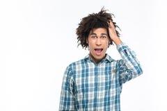 Zadziwiający afro amerykański mężczyzna patrzeje kamerę z kędzierzawym włosy zdjęcie stock