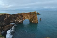 Zadziwiający czerń łuk lawowa pozycja w morzu na małym półwysepie Zdjęcia Royalty Free