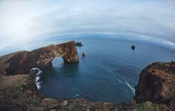 Zadziwiający czerń łuk lawowa pozycja w morzu na małym półwysepie Obrazy Royalty Free