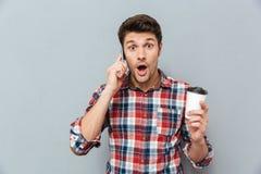 Zadziwiający mężczyzna trzyma takeaway kawę i opowiada na telefonie komórkowym zdjęcia stock