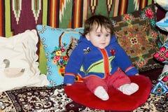 Zadziwiający małej dziewczynki obsiadanie w łóżku na łóżku z upiększonymi poduszkami Zdjęcie Stock