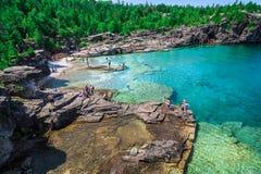 zadziwiający naturalny skalistej plaży widok i spokojni lazur rozjaśniamy wodę z ludźmi w tle Zdjęcie Stock