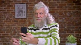Zadziwiający nowożytny dziad opowiada nad sieci kamerą i pokazuje wokoło z jego telefonem w czerwonej cegły biurze podczas gdy by