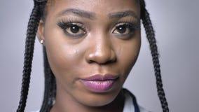 Zadziwiający oczy afrykańska kobieta która patrzeje w kamerze z spokojną i zrelaksowaną twarzą na popielatej folii