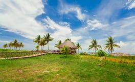 Zadziwiający tropikalny krajobrazowy widok z drewnianym mostem prowadzi plażowy gazebo przeciw niebieskiemu niebu i puszystemu ch Zdjęcia Royalty Free