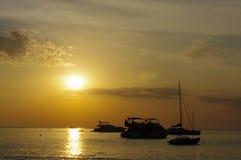 Zadziwiający tropikalny pomarańczowy zmierzch nad wodą, z rockowymi sylwetkami i łodziami na Phuket wyspie, Tajlandia Obrazy Stock