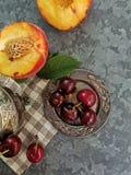 Zadziwiający widok brzoskwinie i wiśnie na stole Jaskrawe, soczyste owoc, i wiśnie - brzoskwinie zdjęcia stock