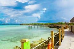 Zadziwiający widok od plażowego molo pokładu na spokojnym oceanie i chmurnego niebieskiego nieba z ludźmi relaksuje w tle Obraz Stock