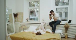 Zadziwiający wygodny projekt w sypialni, jeden para romantycznego czas wpólnie, mężczyzna robi niektóre obrazkom dla damy są zbiory
