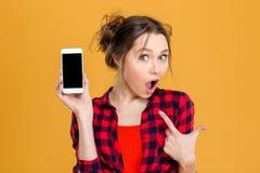 Zadziwiająca kobieta pokazuje pustego smartphone ekran Obrazy Stock