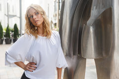 Zadziwiająca blond kobieta z kędzierzawego włosy niedaleką nowożytną rzeźbą outdoors Fotografia Royalty Free