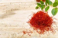 Zafferano rosso con la menta fresca sul piano d'appoggio di legno del tek, spazio della copia Immagini Stock