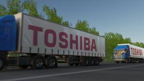 Zafrachtowanie semi przewozi samochodem z Toshiba Corporation loga jeżdżeniem wzdłuż lasowej drogi Redakcyjny 3D rendering Zdjęcie Royalty Free