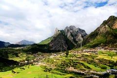 Zagana, ein tibetanisches Dorf umgeben durch Berge Lizenzfreie Stockfotos