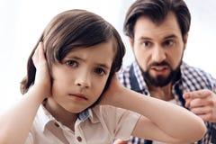 Zagniewany ojciec łaja nastoletniego syna który czopuje ucho zdjęcie stock