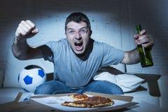 Zagorzałego szalonego fan piłki nożnej dopatrywania telewizyjna piłka nożna krzyczy szczęśliwą odświętność zdobywa punkty cel Obraz Stock