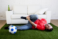 Zagorzały fan piłki nożnej na zielonej trawy dywanie naśladuje stadium piłkarski smołę wyśmiewa gracza w bólu krzywdzi na kostce obraz stock