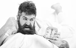 Zagraża jego rękę przy budzikiem, próba niszczyć Czuciowy wściekły Gniewny facet w łóżku w ranku Zdjęcie Stock