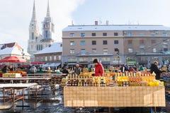 Zagreb, Croácia: 7 de janeiro de 2016: Suporte com vidros do mel no mercado de Dolac durante o inverno com neve com a catedral na Imagens de Stock