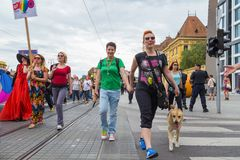 15th Zagreb pride. LGBTIQ activists on street. ZAGREB, CROATIA - JUNE 11, 2016: 15th Zagreb pride. LGBTIQ activists walking the dog decorated with rainbow stock photography