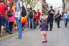 15th Zagreb pride. Little kid on the street next to LGBTIQ activists. ZAGREB, CROATIA - JUNE 11, 2016: 15th Zagreb pride. Little kid on the street next to stock photo