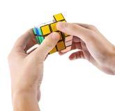 ZAGREB, KROATIË - MAART 13, 2015: Handen die de Kubus van Rubik oplossen De Kubus van Rubik wordt uitgevonden door Erno Rubik in  Stock Foto's