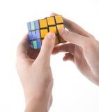 ZAGREB, KROATIË - MAART 13, 2015: Handen die Rubiks-Kubus oplossen De Rubikskubus wordt uitgevonden door Erno Rubik in 1974 Hij i Stock Foto's