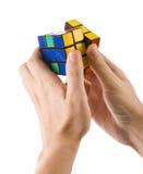 ZAGREB, KROATIË - MAART 13, 2015: Handen die Rubiks-Kubus oplossen De Rubikskubus wordt uitgevonden door Erno Rubik in 1974 Hij i Stock Fotografie