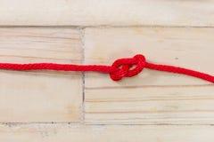 Zahl-acht Knoten gemacht mit rotem Seil auf hölzernem Hintergrund Stockbilder